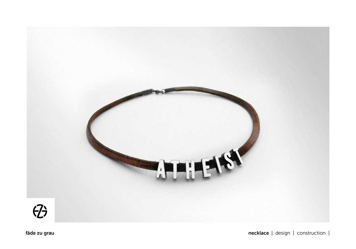 "brown leather band necklace with white painted metal letters spelling ""atheist"""