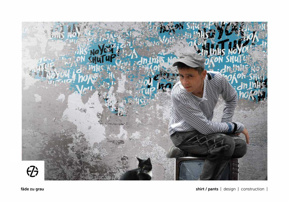 artist fade zu grau in a striped shirt sitting on a broken tv set with his black cat in front