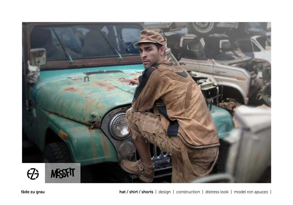male fashion model in a junk yard presents brown hat, brown shirt and brown shorts