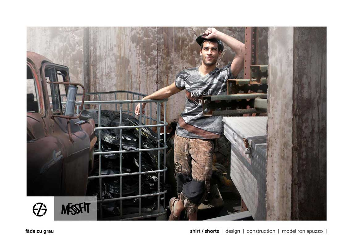 male fashion model in a junk yard presents gray brown t-shirt and brown shorts