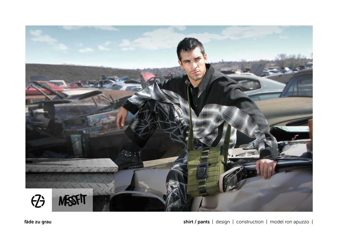 male fashion model in a junk yard presents black and white shirt and pants and green bag