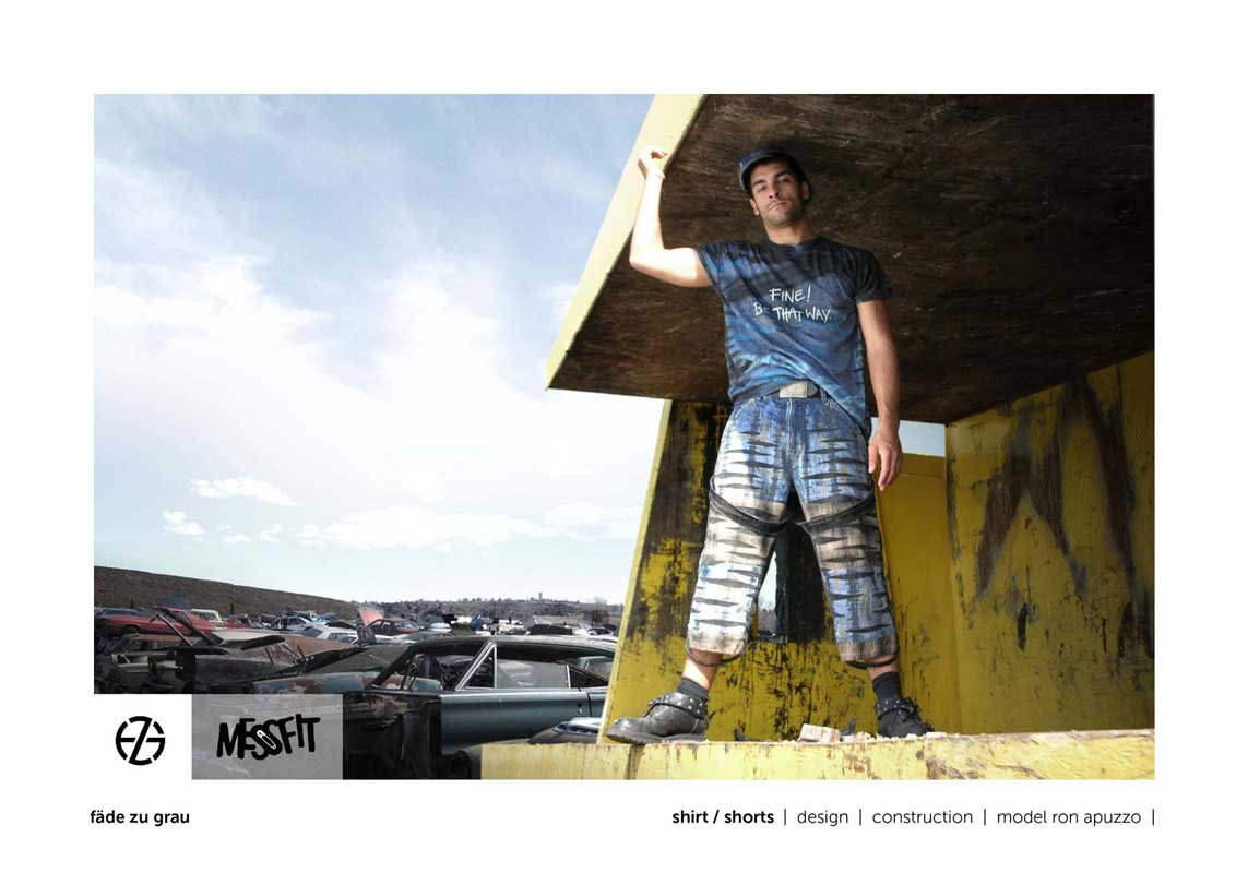 male fashion model in a junk yard presents blue t-shirt and blue jeans shorts